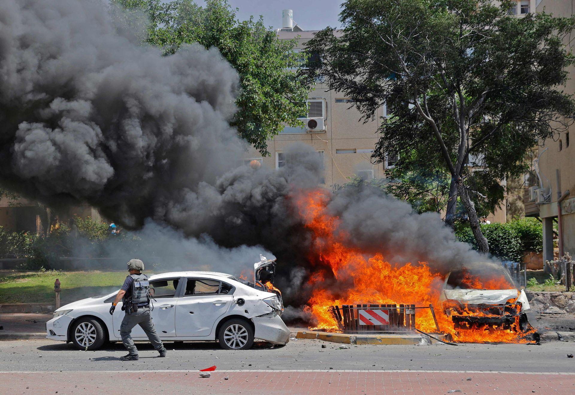 Un soldado de Isaeli pasa corriendo junto a un auto en llamas después de ser alcanzado por un misil