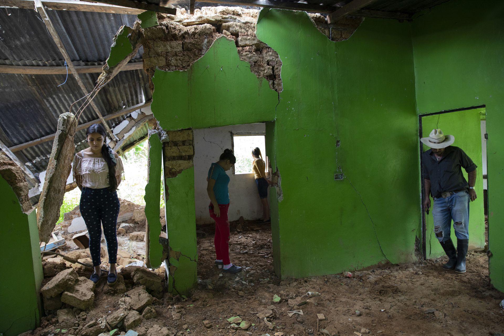 """Marian Castron, 23; Maria Castron, 25; Jenny Castron, de 19 años, y Omar Castron, de 50, visitan su casa devastada por un deslizamiento de tierra.""""Planeamos regresar, pero será imposible """", dice Omar"""