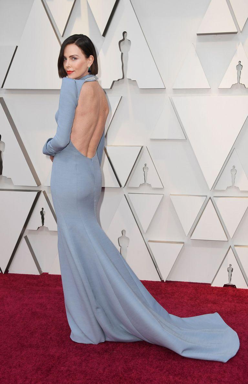 Charlize Theron, en un vestido alta costura Dior con pronunciado escote en la espalda y larga cola; las joyas son Burberry