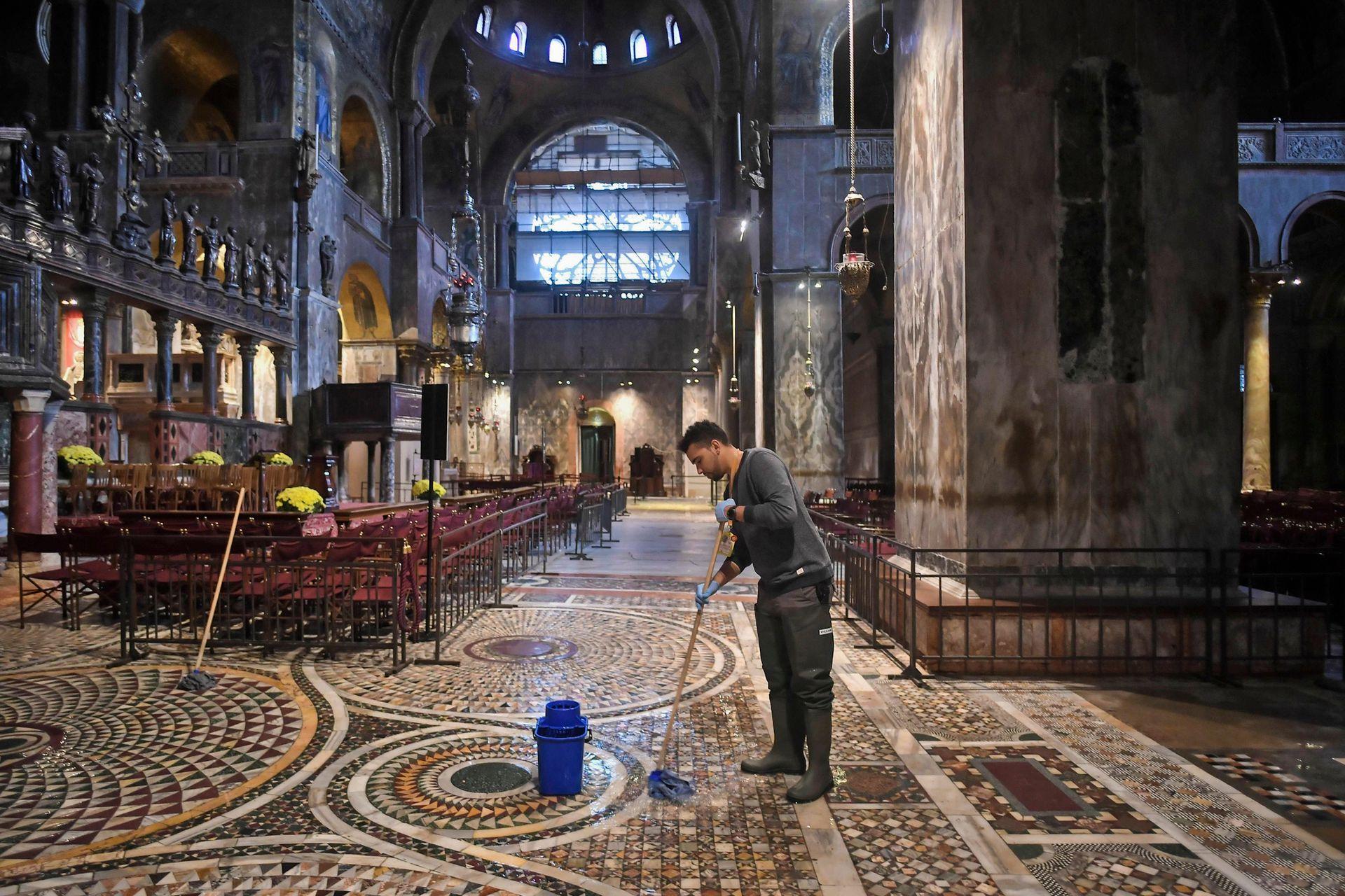 Un hombre trapea el piso de la Basílica de San Marcos inundada después de un excepcional nivel de agua durante la marea alta