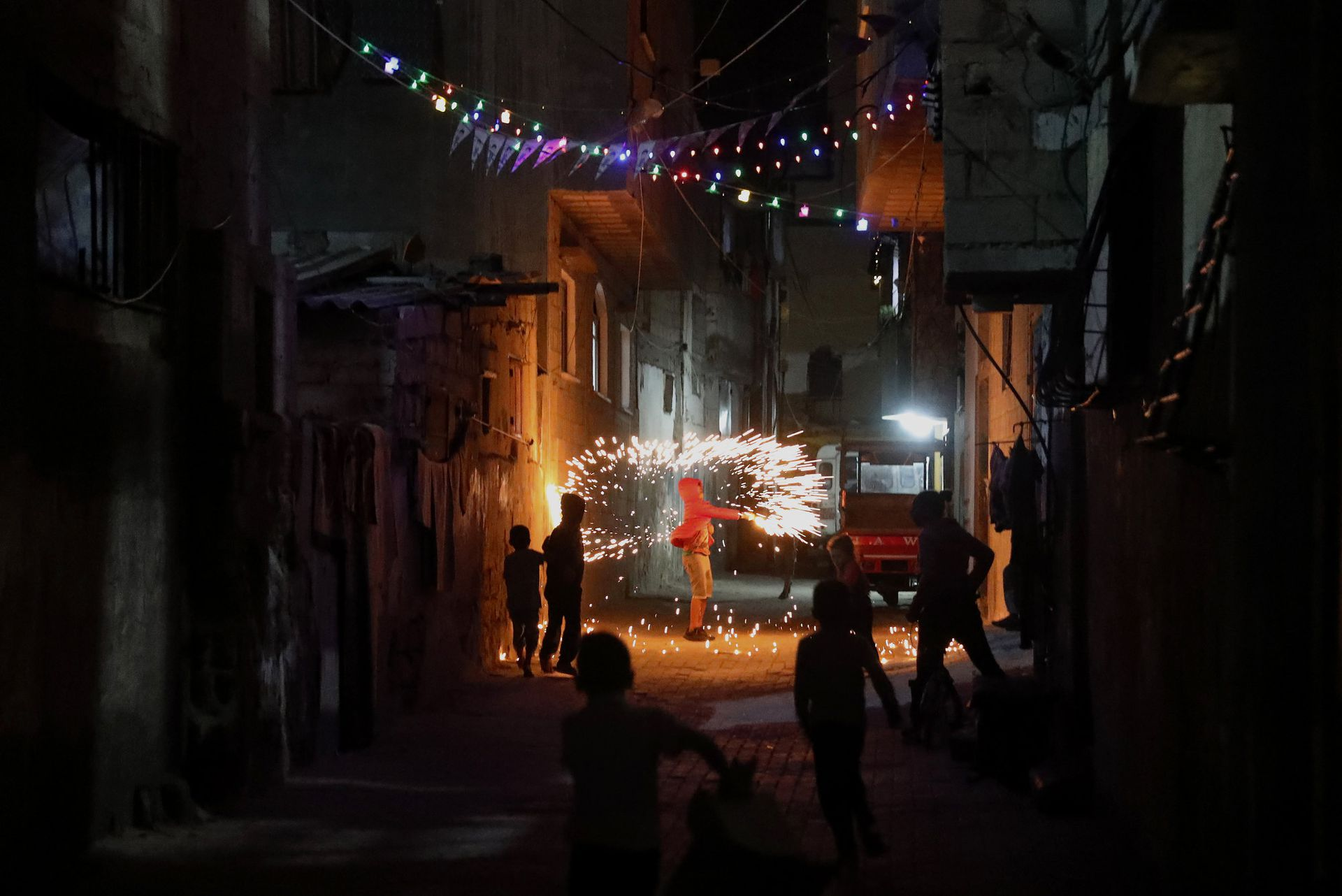 Este martes 20 de abril, un grupo de niños juega con fuegos artificiales, a lo largo de un callejón en la ciudad de Gaza, mientras celebran frente a las casas de sus familias