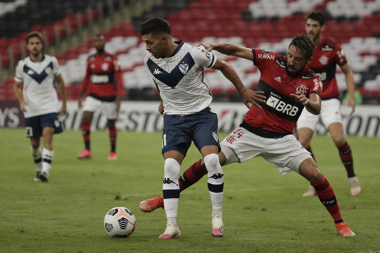 Lucas Janson ante Mauricio Isla; no se sacaron ventajas entre Vélez y Flamengo, en Río de Janeiro, por la Copa Libertadores