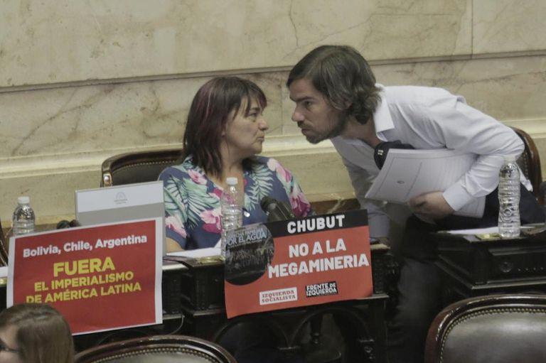 Dos diputados de Izquierda junto a los carteles que exhiben hoy en sus bancas