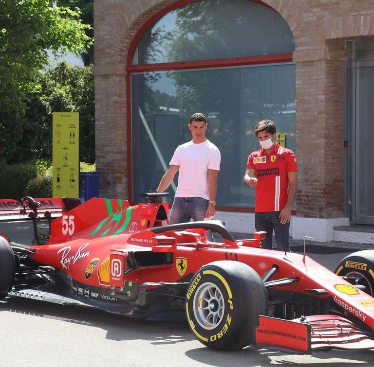 Cristiano y Carlos Sainz junto a la nave de Ferrari que compite en Fórmula 1