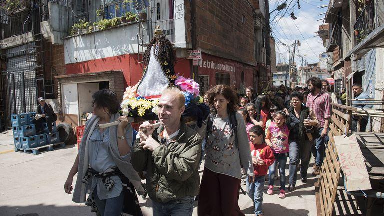 El público participa de una procesión religiosa en la calle, como parte de la obra