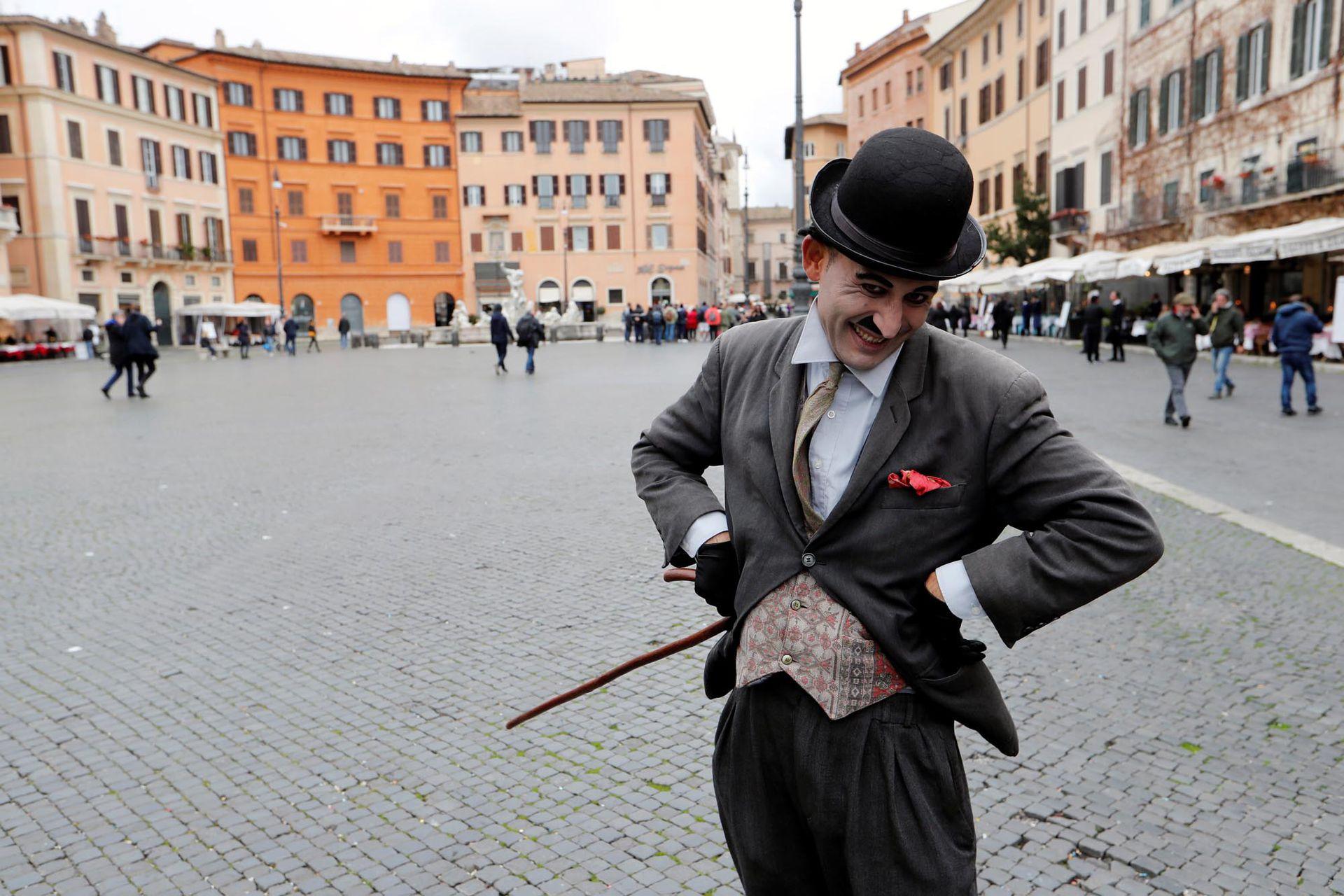 Un hombre vestido como Charlie Chaplin posa para una fotografía en una Piazza Navona casi vacía, que generalmente estaría llena de turistas, en Roma, Italia, el 2 de marzo de 2020