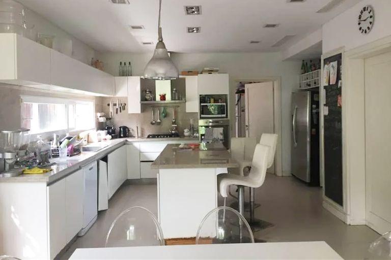 La cocina tiene isla central, luces empotradas y alacenas a medida