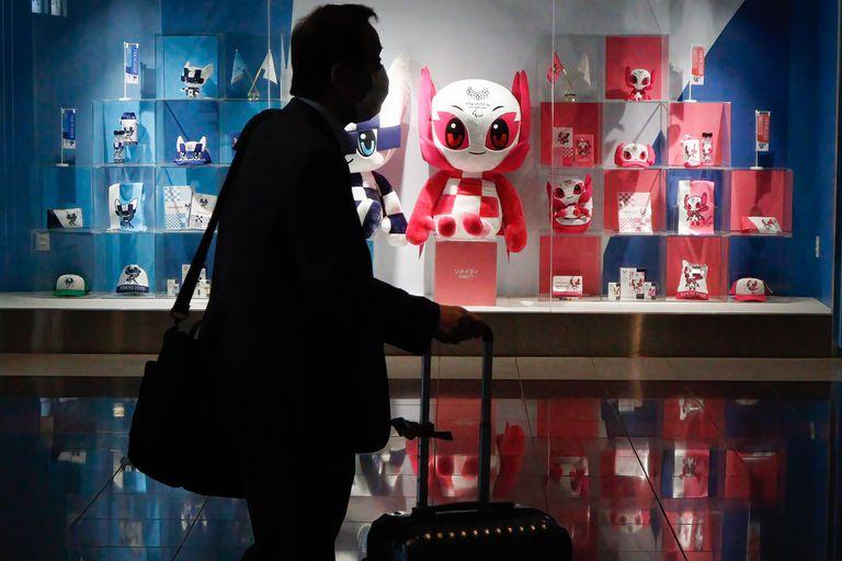 Un hombre que llevaba una máscara protectora pasa por la Tienda Olímpica Oficial de Tokio en el Aeropuerto Internacional de Tokio Haneda.
