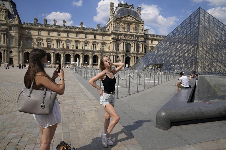La alemana Paula Wei, derecha, es fotografiada el miércoles 9 de junio de 2021 por una amiga francesa frente al museo del Louvre, en París. (AP Foto/Francois Mori)