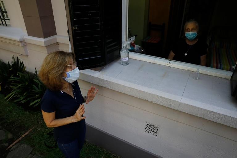 Claudia Brañeiro, de 66 años, habla con su madre, Rosa Guglietti, de 90. Tienen que dialogar desde la ventana que da a la calle para cumplir con el protocolo COVID_19 FOTO: RICARDO PRISTUPLUK