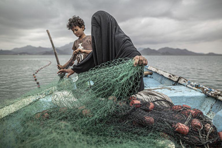 """Imagen del argentino Pablo Tosco, titulada """"Yemen: el hambre, otra herida de guerra"""", que ganó el primer premio en la categoría Temas Contemporáneos. Muestra a Fátima y su hijo preparando una red de pesca en un barco en la bahía de Khor Omeira, Yemen, el 12 de febrero de 2020"""