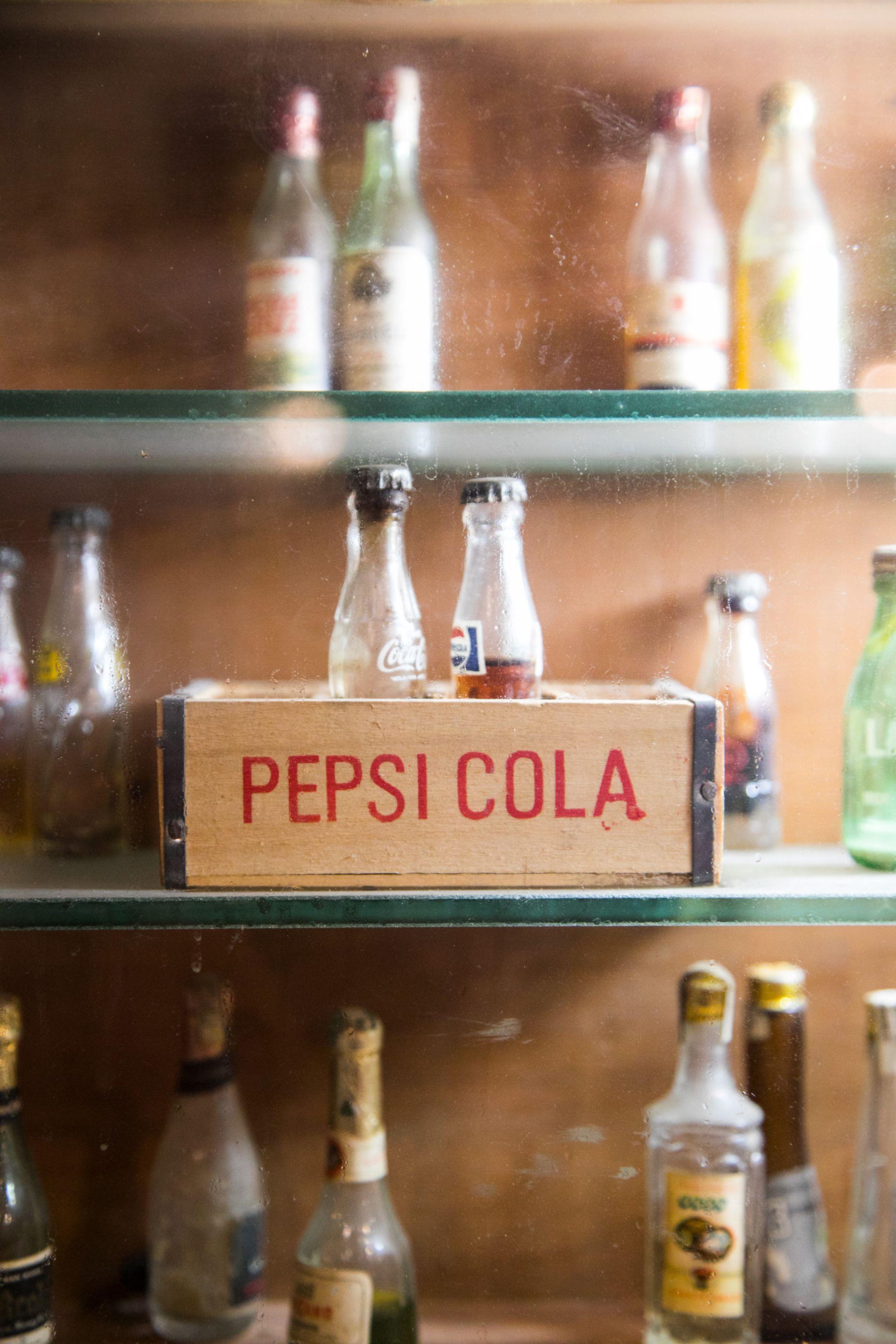 Antiguas botellas en las vitrinas de La Protegida en Navarro.