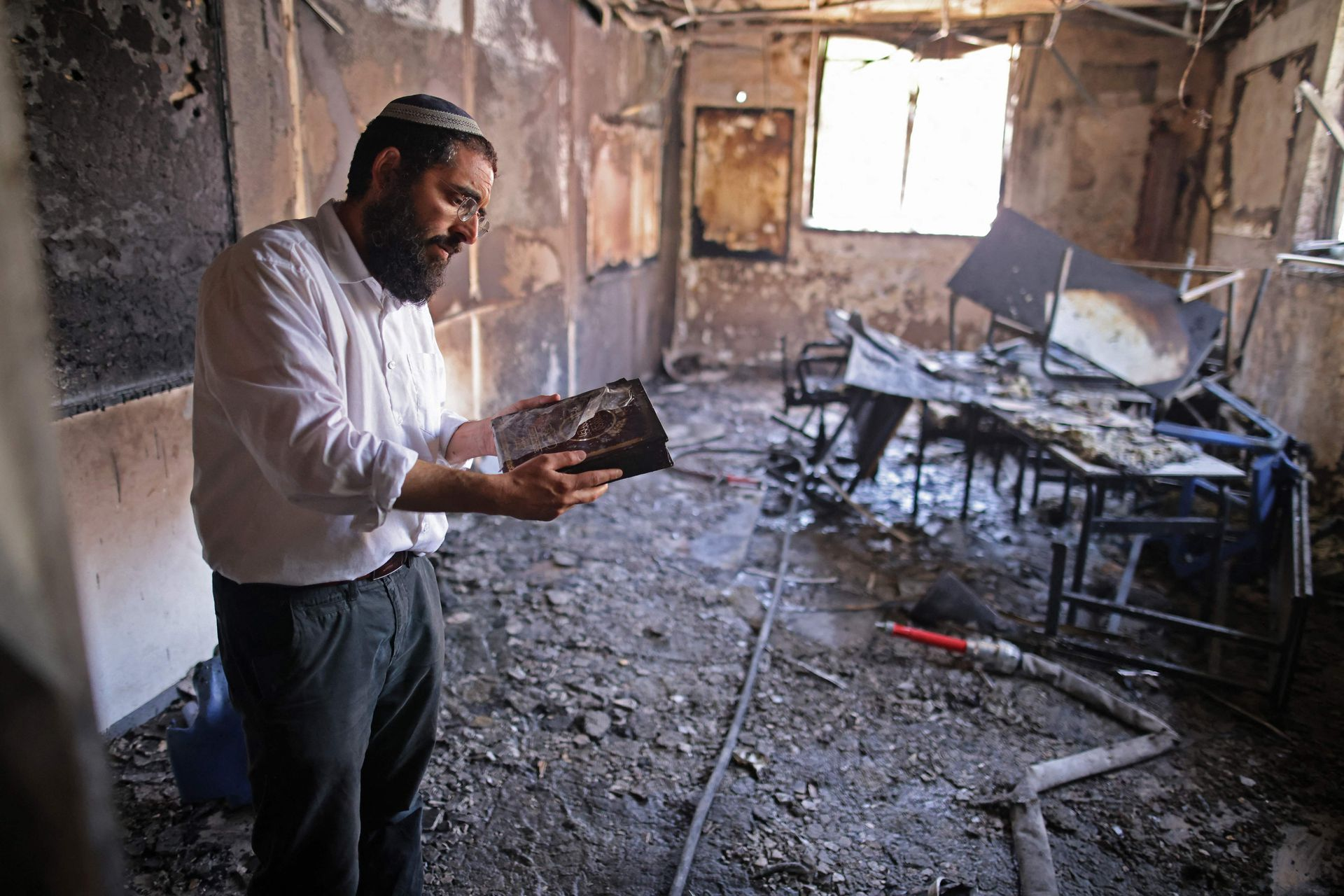 Un rabino inspecciona los daños dentro de una escuela religiosa incendiada en la ciudad central israelí de Lod, cerca de Tel Aviv