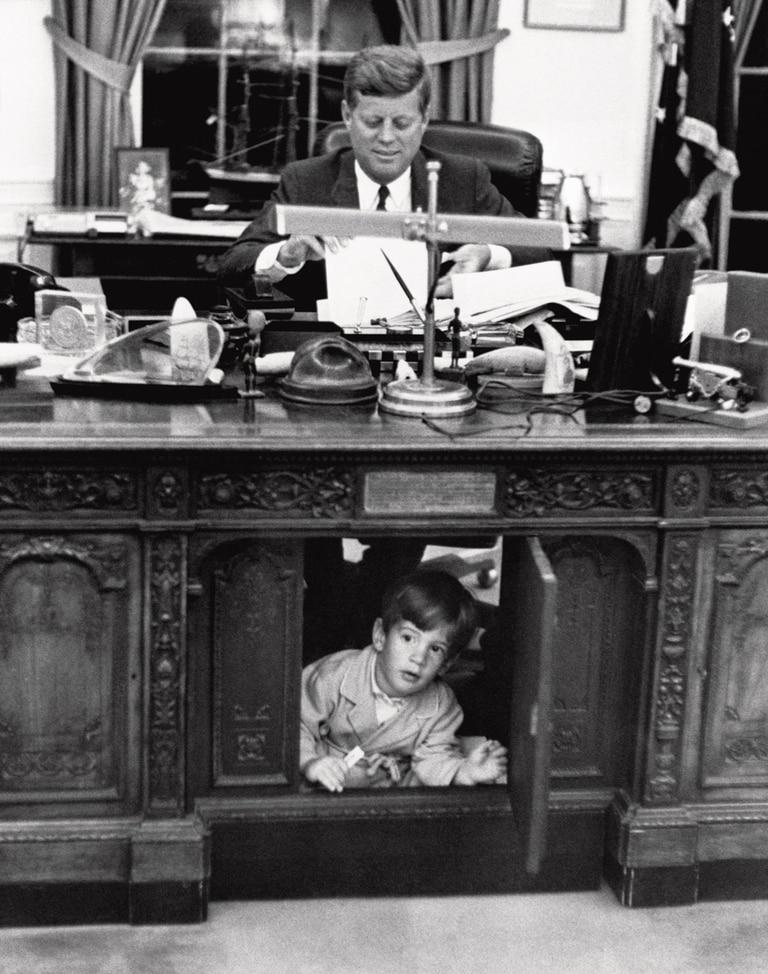 Una famosa imagen tomada en 1962, donde John John se esconde debajo del escritorio de su padre, el presidente demócrata, John F. Kennedy.