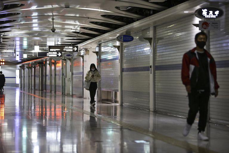 Unas personas caminan por una zona de comercios en el subterráneo cerrados debido a la emergencia por el coronavirus en Osaka, Japón, el 25 de abril de 2021