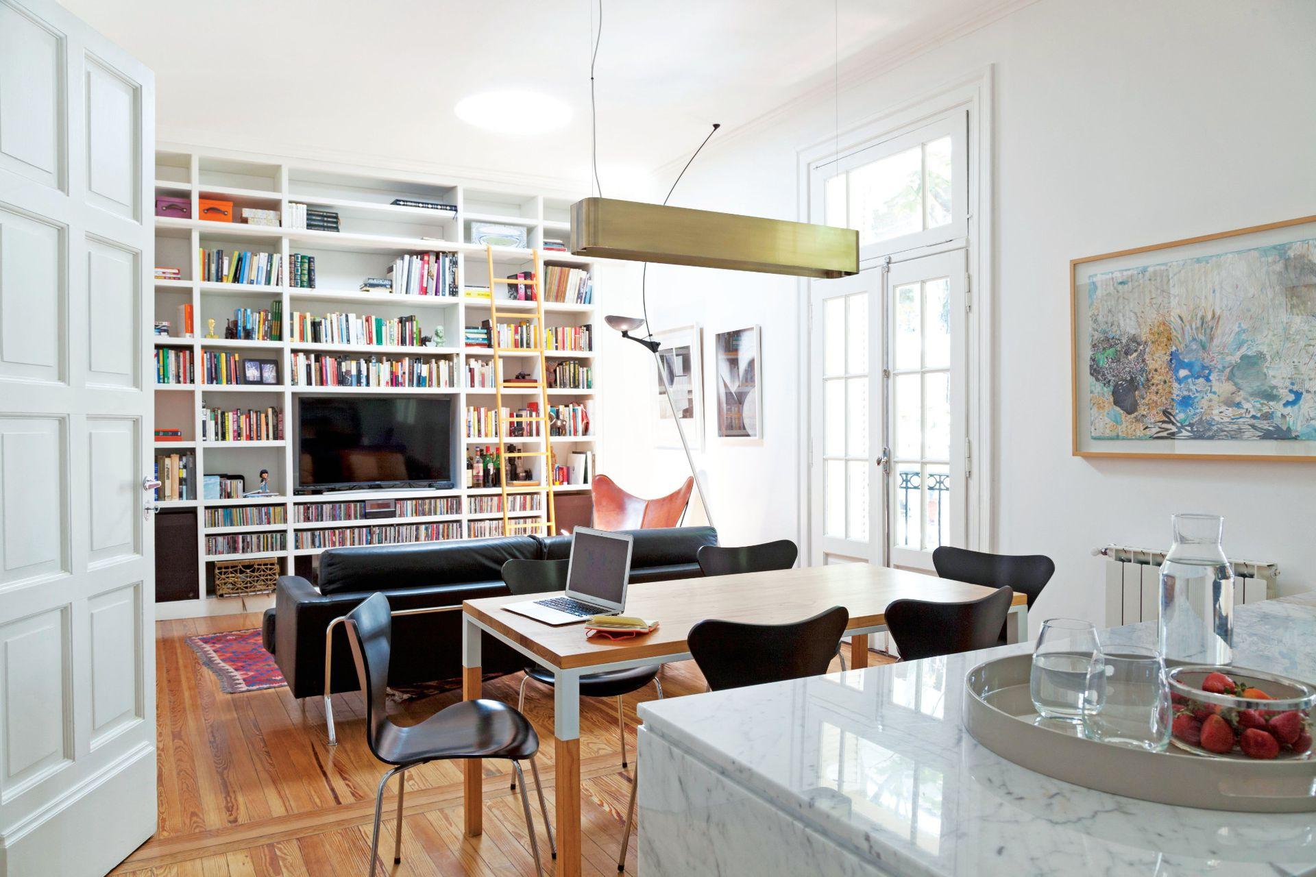 Detrás de la silla BKF, un regalo para la arquitecta: obras de Platz (Galería Praxis). La biblioteca con escalera (Estudio Trama) abarca la totalidad de la pared lateral.