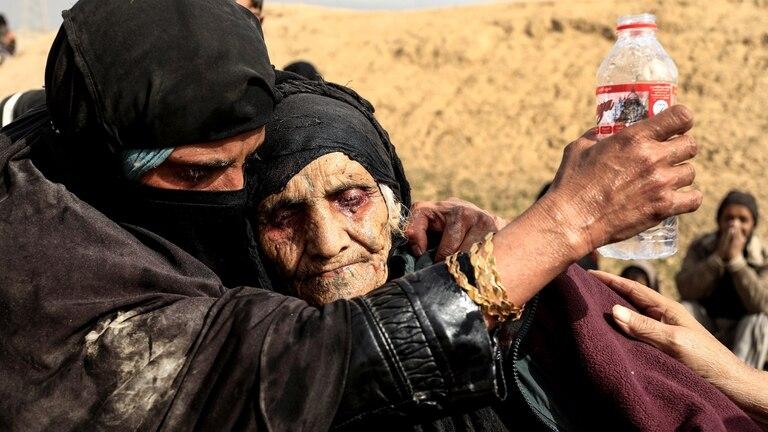 Mujeres iraquíes desplazadas que acaban de huir de su hogar descansan en el desierto mientras esperan ser transportadas mientras las fuerzas iraquíes luchan contra militantes del Estado Islámico en el oeste de Mosul, Irak, 27 de febrero
