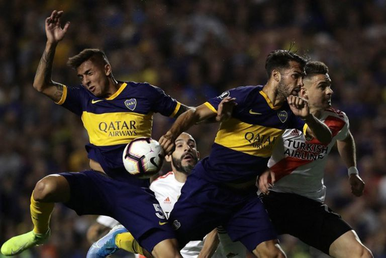 Players of Boca Juniors (Blue and yellow) and River Plate jump for the ball during their all-Argentine Copa Libertadores semi-final second leg football match at La Bombonera stadium in Buenos Aires, on October 22, 2019. (Photo by Alejandro PAGNI / AFP)