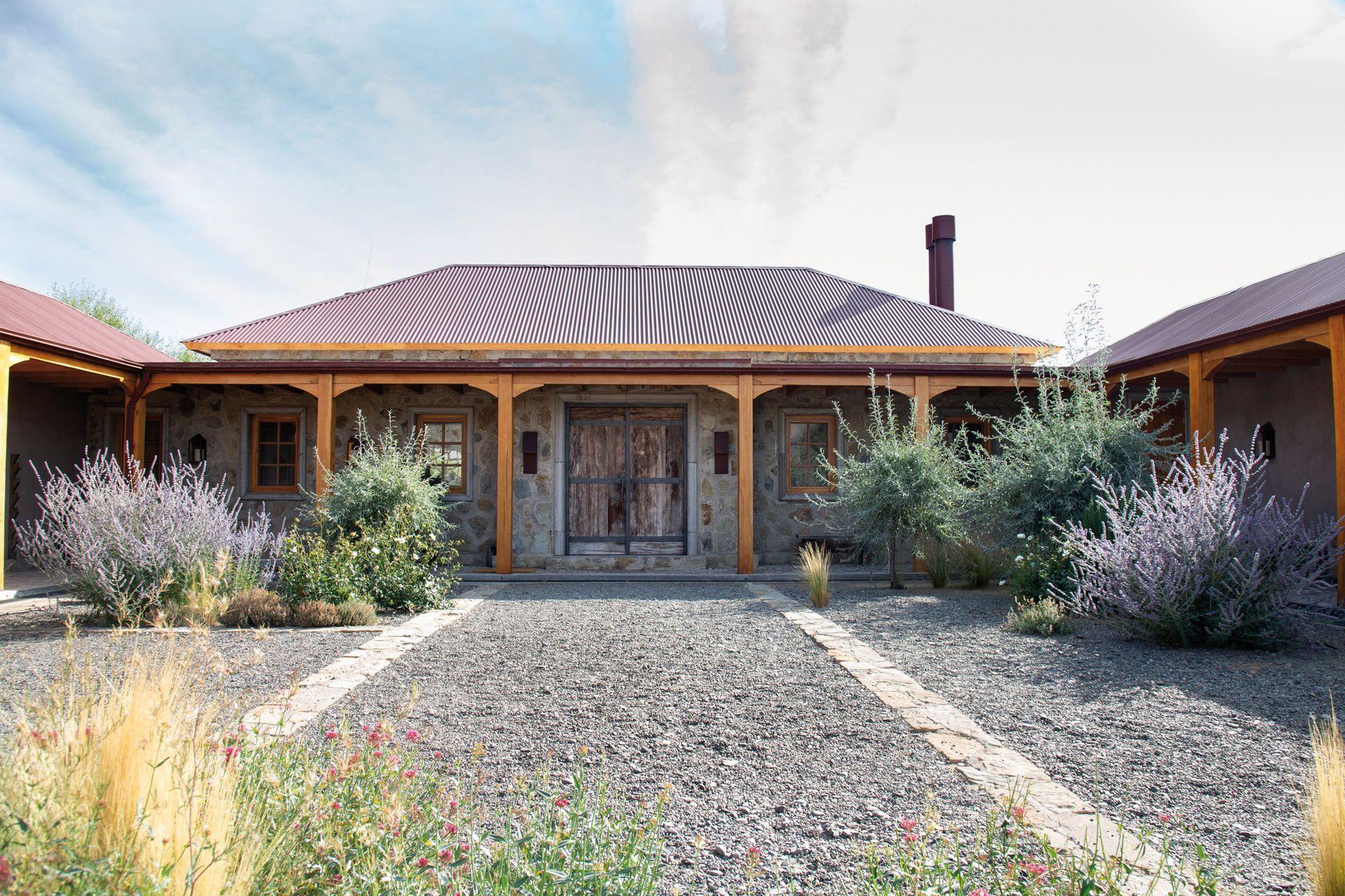 El patio de entrada enmarca la puerta principal con un fuerte dibujo sobre la granza. Allí se plantaron Pyrus salicifolia 'Pendula' de follaje gris, perovskias, nepetas, romeros y gramíneas que se engaman con los colores de la casa.