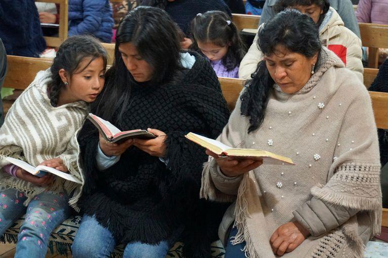 La futura primera dama de Perú, Lilia Paredes, derecha, lee la Biblia junto a su hermana menor Yenifer y la hija de ésta, Alondra, de 9 años, durante una ceremonia religiosa el jueves 22 de julio de 2021 a la que fueron invitados los vecinos para despedirse de la familia antes de que parta hacia Lima, en la iglesia del Nazareno, en Chugur, Perú.