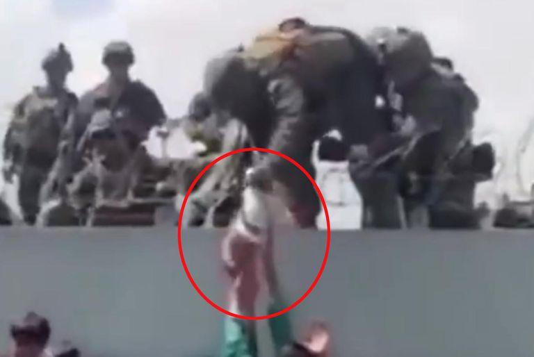 Un bebé es entregado sobre el muro del aeropuerto de Kabul a las tropas estadounidenses