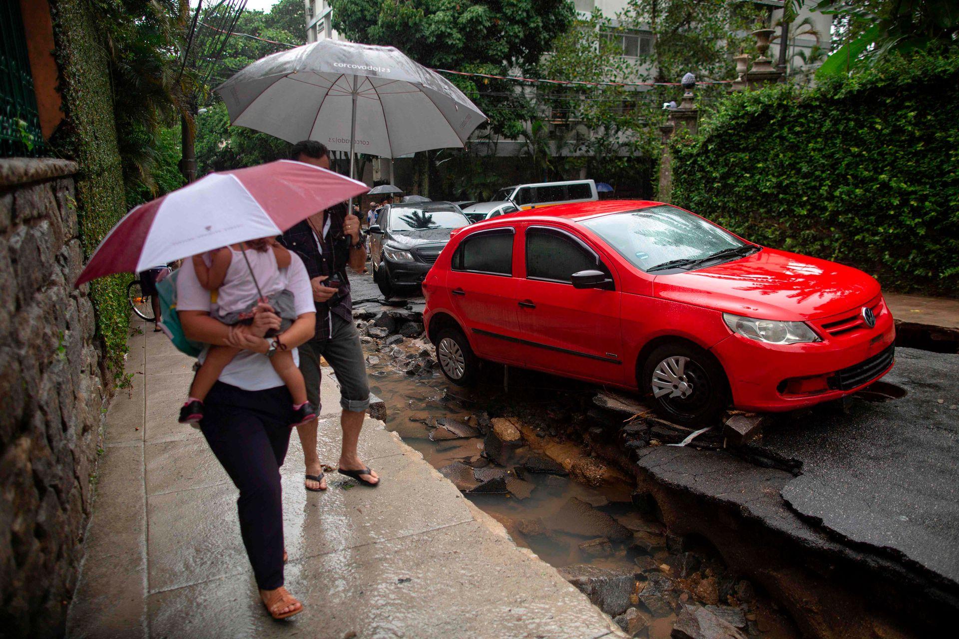 La gente camina por una calle dañada después de fuertes lluvias en el barrio Jardim Botanico en Río de Janeiro