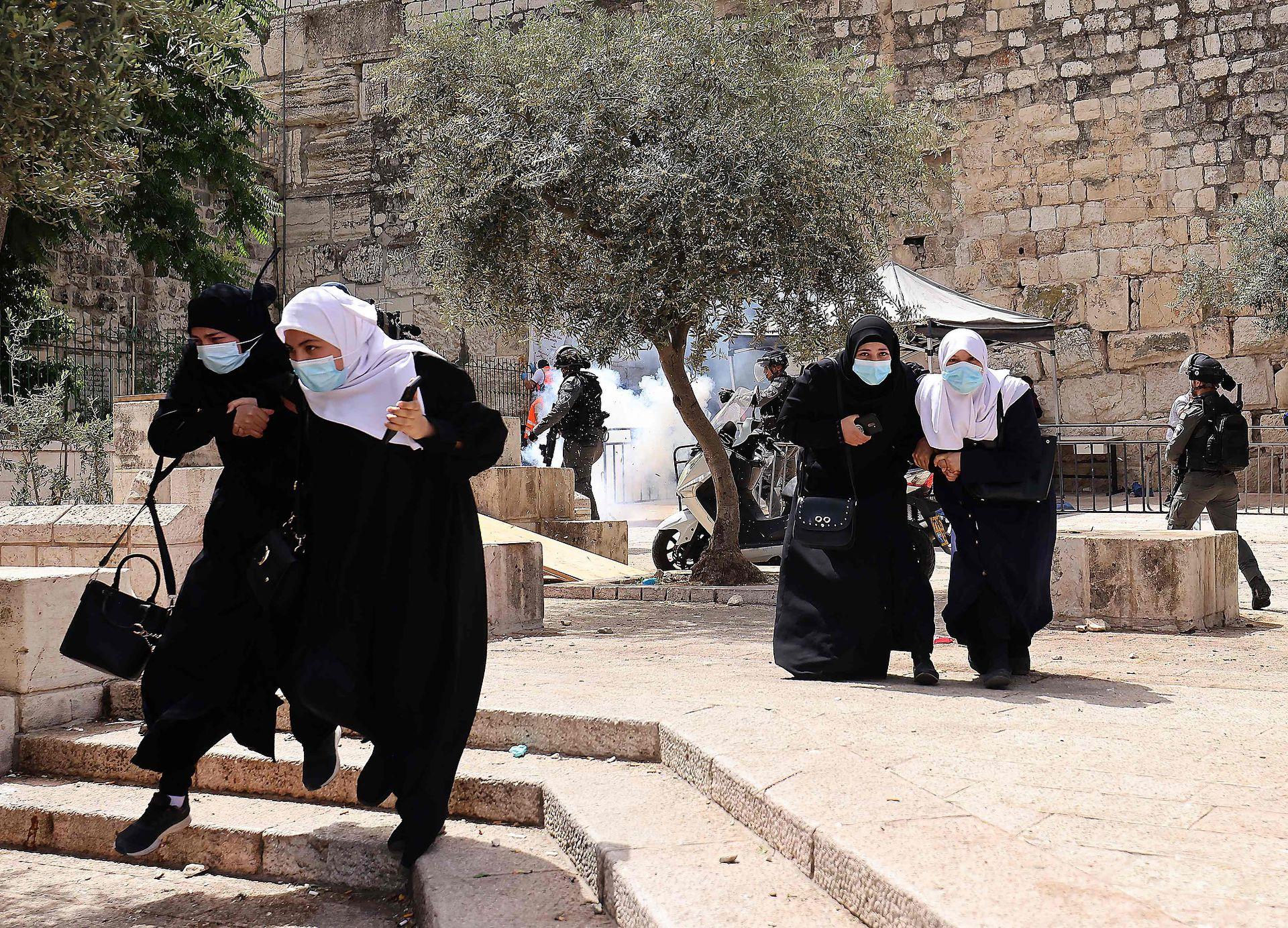 Mujeres palestinas corren a resguardarse de gas lacrimógeno lanzado por fuerzas de seguridad israelíes en la Ciudad Vieja de Jerusalén, el 10 de mayo de 2021