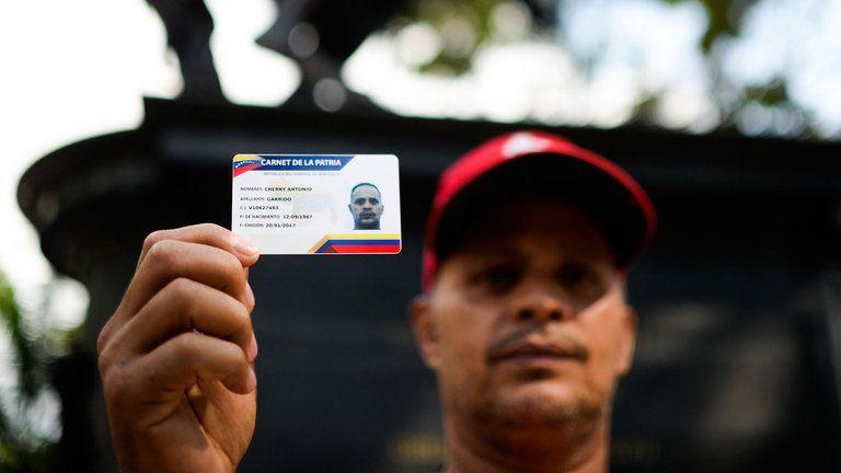 Un hombre muestra el carnet de la Patria, que permite adquirir alimentos y otros productos a precios subsidiados en Venezuela