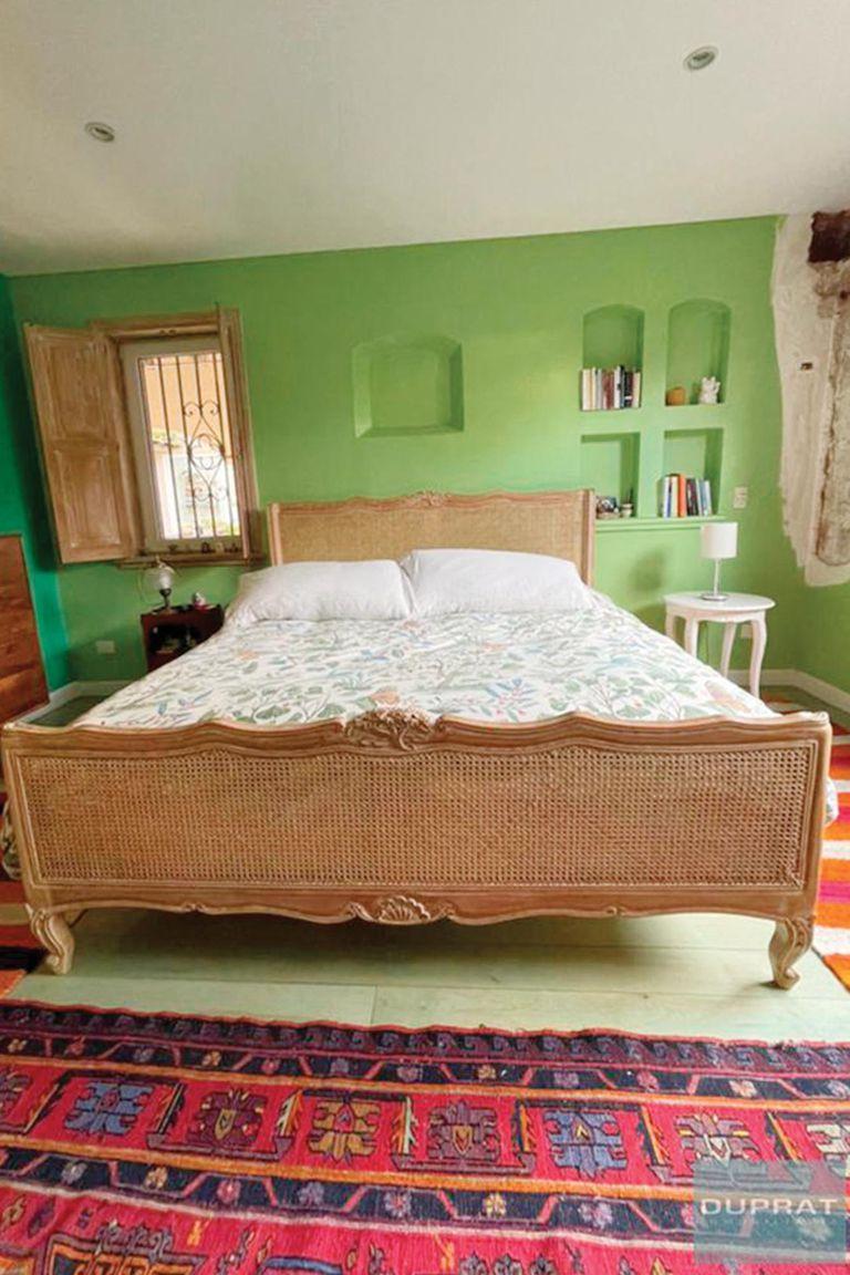 Una de las suites, con cama provenzal con respaldo de esterilla y alfombras coloridas.