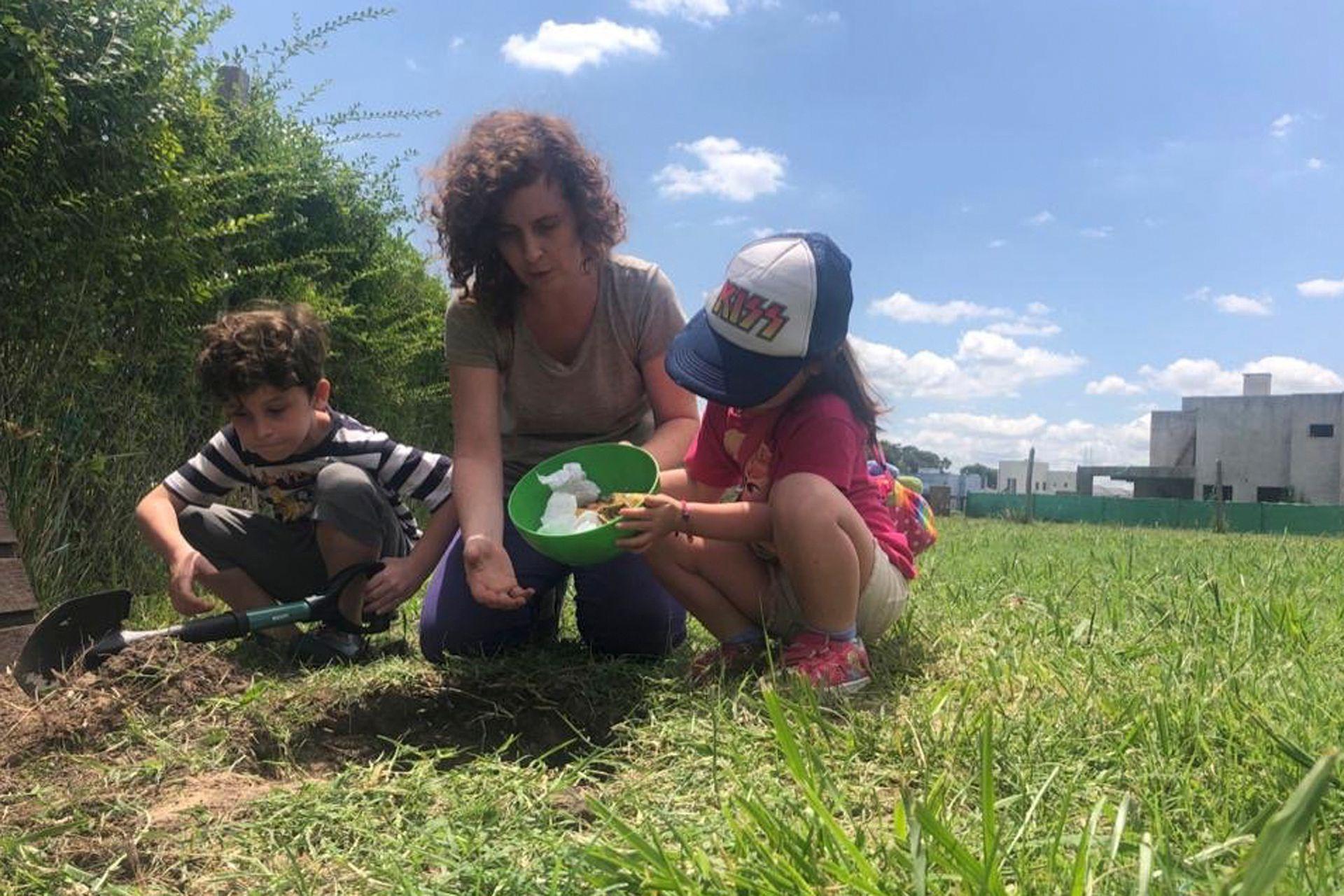 Mariel Klosewicz junto a sus hijos Lorenzo y Renata haciendo tareas de huerta en el jadín de su casa