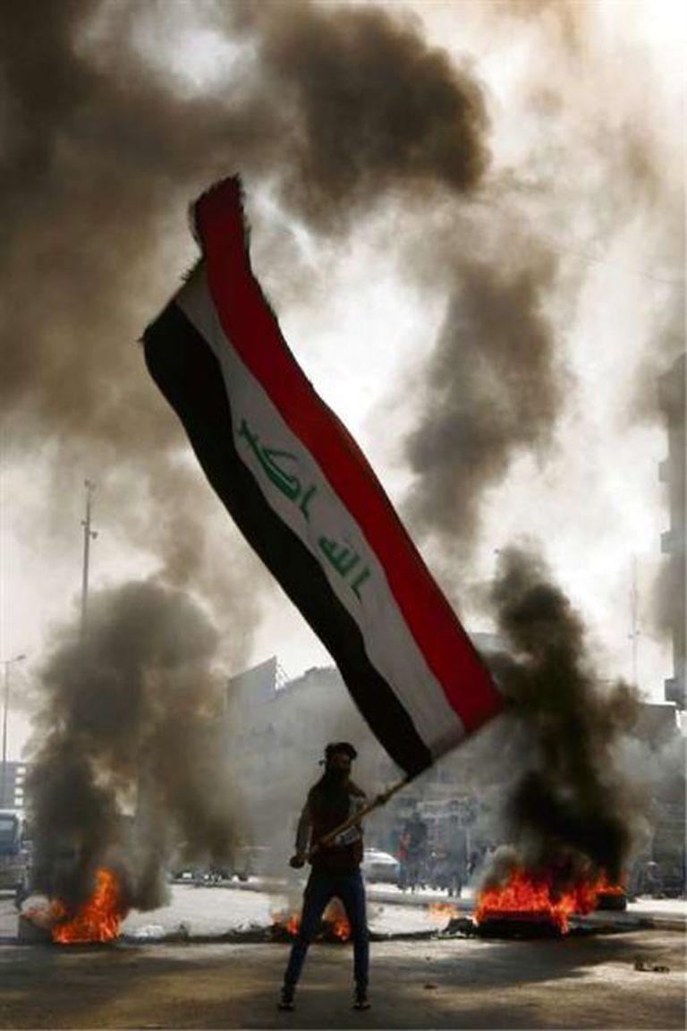 Un manifestante con una bandera en Najaf