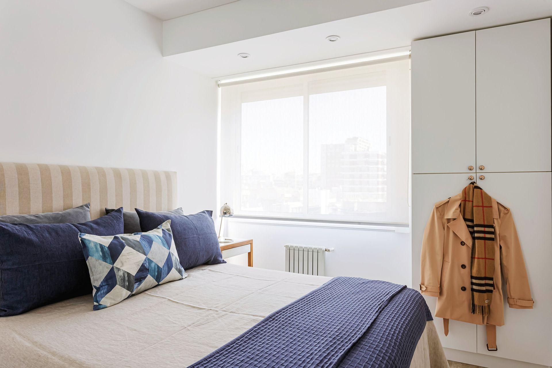 En la cama, cubreedredón de lino beige, manta tejida azul y almohadón estampado (Ramos Generales). Mesas de luz (Eugenio Aguirre).