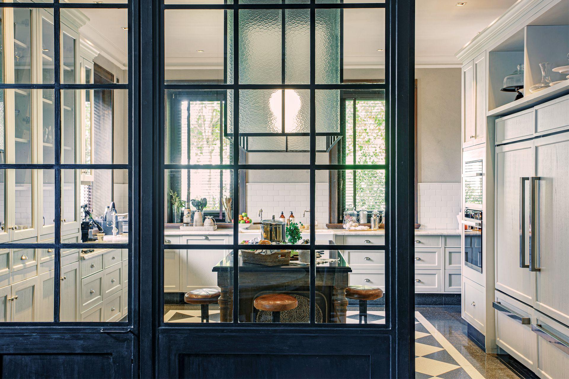 Mesa recuperada (Amighini). Tapa (Ragolia). Campana de vidrio martelé con perfilería de hierro (Estudio Pablo Chiappori). Banquetas a medida (AG Art & Design).
