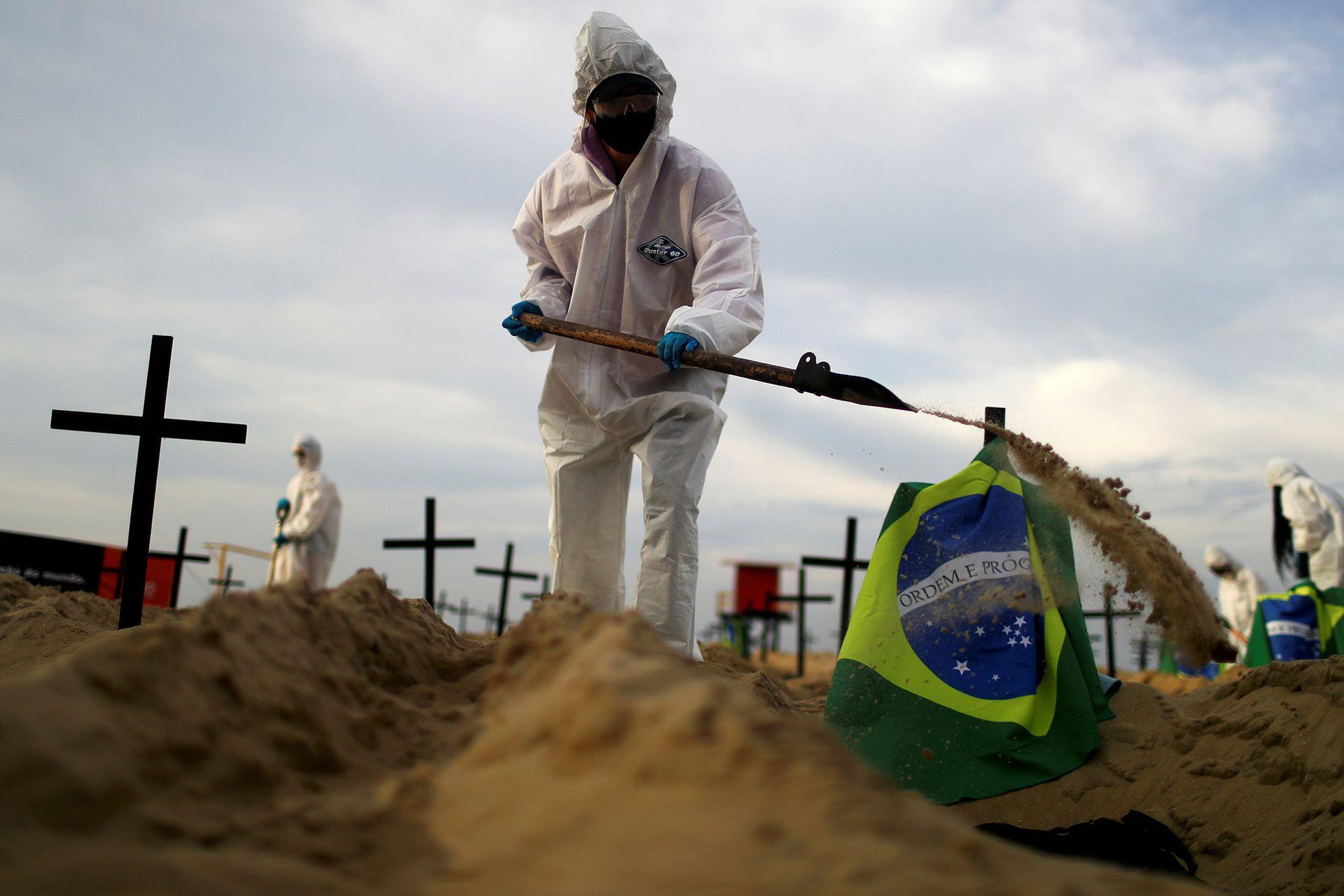 Un activista de la ONG Río de Paz, con un traje protector, cava tumbas en la playa de Copacabana para simbolizar a las víctimas del coronavirus