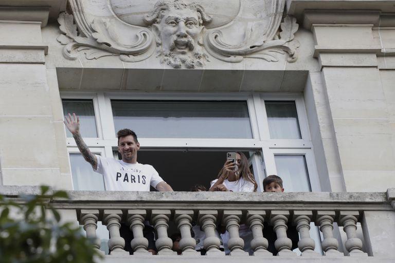 Messi saluda a sus seguidores desde el balcón de su hotel mientras su esposa, Antonela Roccuzzo, toma fotografías: ocurrió en París, el 10 de agosto, cuando iniciaron su nueva vida