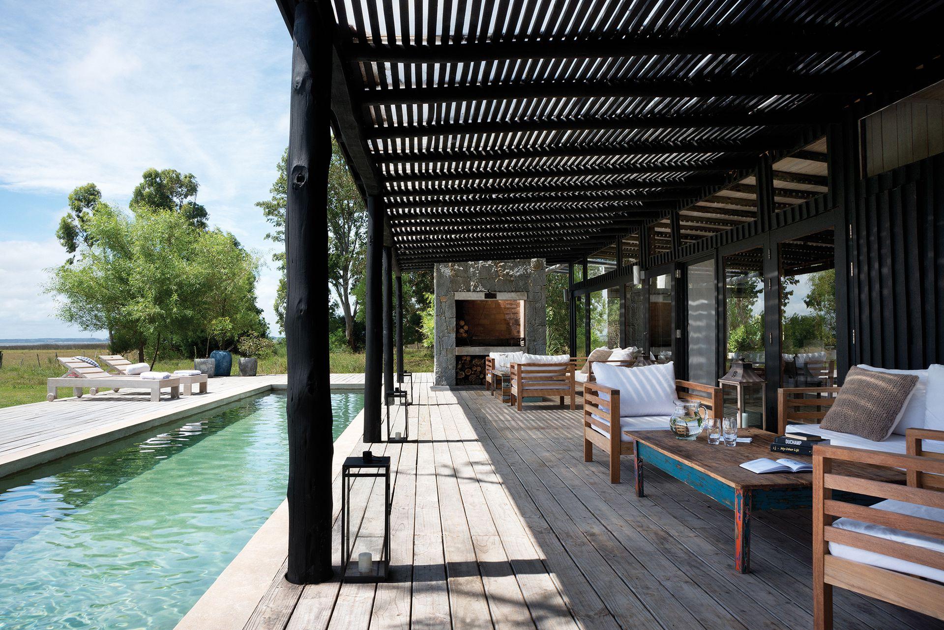 """Frente a la casa principal, una pileta tipo """"lap pool"""" construida íntegramente en cemento y estucada frente al deck de pino tratado."""