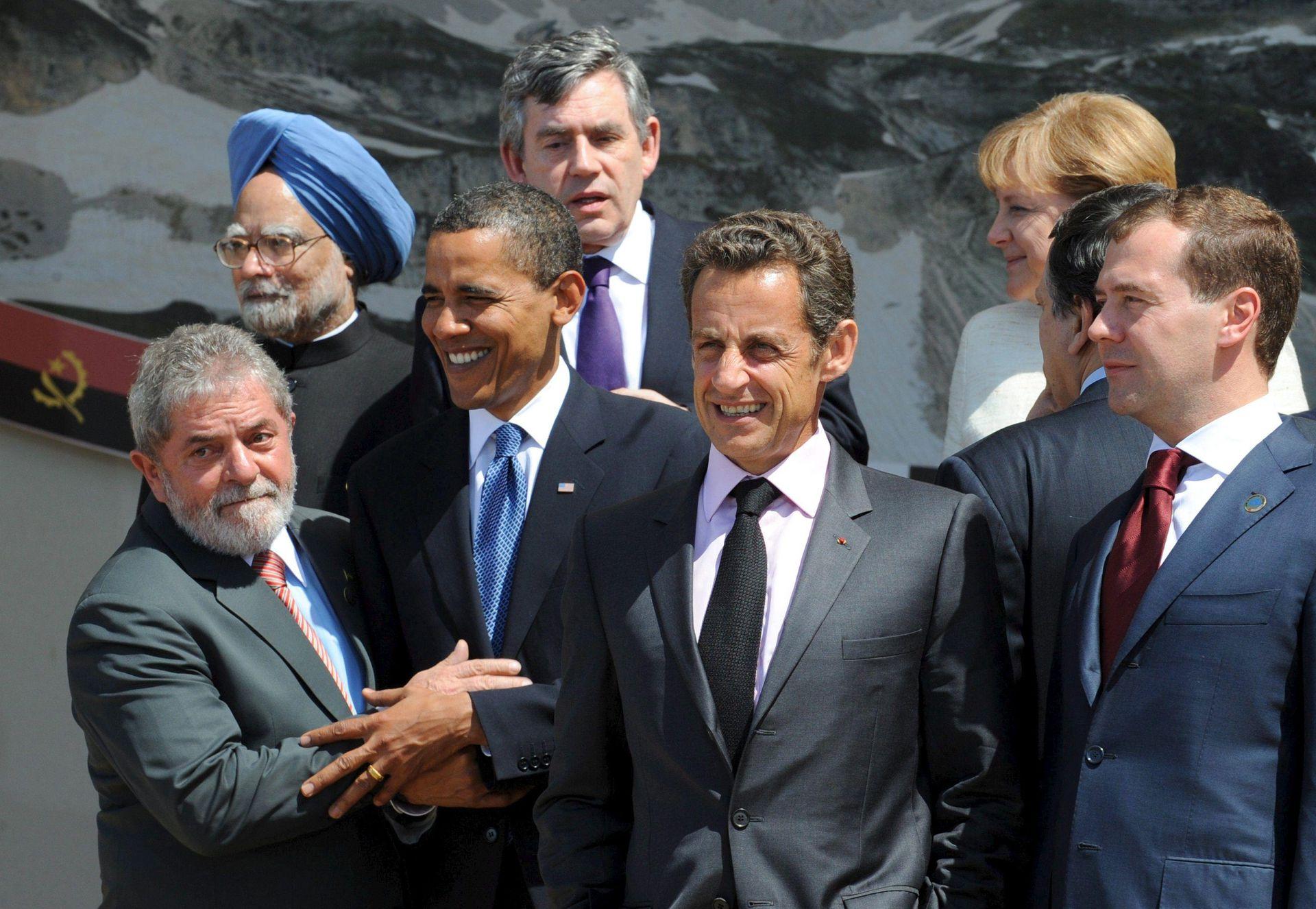 De izquierda a derecha, delante, el presidente brasileño, Luiz Inacio Lula da Silva; el presidente estadounidense, Barack Obama; el presidente francés, Nicolas Sarkozy; y el presidente ruso, Dmitri Medvedev; y de izquierda a derecha, detrás, el primer ministro indio, Manmohan Singh, el primer ministro británico, Gordon Brown, y la canciller alemana, Angela Merkel, bajan del podio después de posar para una foto de familia de los líderes del G-8 en la localidad italiana de L' Aquila el 9 de julio de 2009