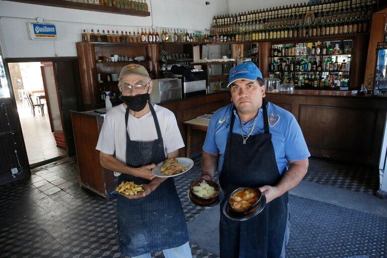 """""""Pupi"""" Portillo, encargado, y Ramón Agüero, cocinero, con dos de los platos preferidos de La Flor de Barracas"""
