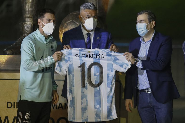 Argentine footballer Lionel Messi (L), the president of the Argentine Football Association (AFA), Claudio Tapia (C), and the governor of Santiago del Estero Province, Gerardo Zamora, display a jersey of the national team with Zamora's name after unveiling a five-metre statue of late Argentine football star Diego Armando Maradona, outside the Estadio Unico Madre de Ciudades stadium in Santiago del Estero, Argentina, on June 3, 2021, before the South American qualification football match for the FIFA World Cup Qatar 2022 between Argentina and Chile. (Photo by AGUSTIN MARCARIAN / POOL / AFP)