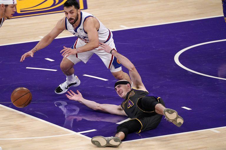 Alex Caruso, de los Lakers de Los Ángeles, y el argentino Facundo Campazzo, de los Nuggets de Denver, a la izquierda, disputan un balón suelto durante la segunda mitad del partido en Los Ángeles, el lunes 3 de mayo de 2021. (AP Foto/Mark J. Terrill)