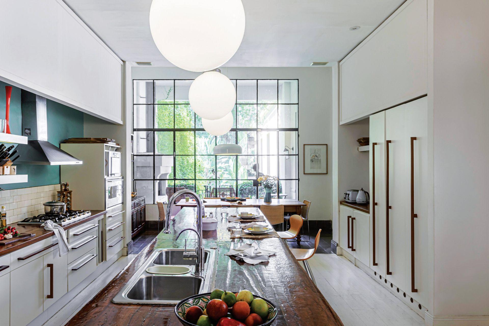 El piso de madera de la cocina se prolonga en calcáreos en el comedor diario. El cerramiento de hierro y vidrio repartido es parte de la reforma anterior. Da a la chimenea-parrilla y al jardín.