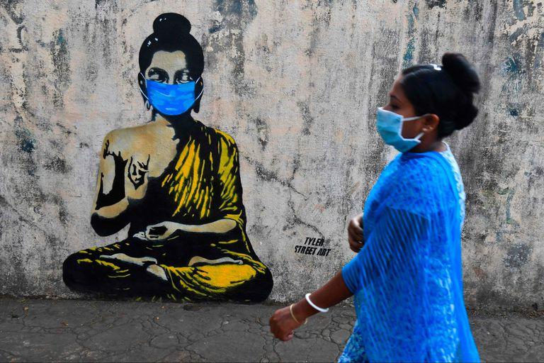 Un grafitti de Buddha con una barbijo en Mumbai