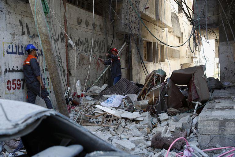 Los trabajadores inspeccionan los escombros del edificio destruido de Abu Hussein que fue alcanzado por un ataque aéreo israelí la mañana del 19 de mayo de 2021