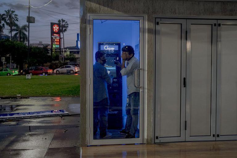 Kevin Martinez, de 26 años, a la izquierda, y Harold Valle, de 32 años, intentan enviar dinero a través de un cajero automático Chivo en San Salvador