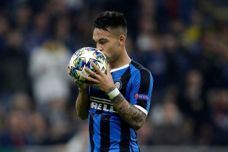 Lautaro Martínez besa la pelota antes de ejecutar el penal que le atajó el arquero de Borussia Dortmund. Antes había anotado un gol.