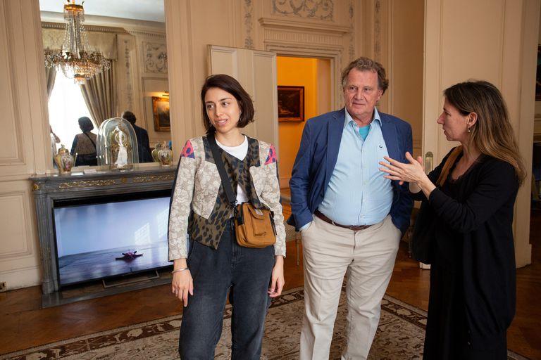 Anfitrión, el embajador Sersale junto con la curadora Melina Berkenwald (URRA) y Camila Charask; como en cada rincón, en la chimenea, una pantalla