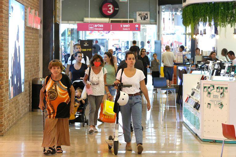 Personas hacen compras sin mascarilla en un centro comercial en Tel Aviv