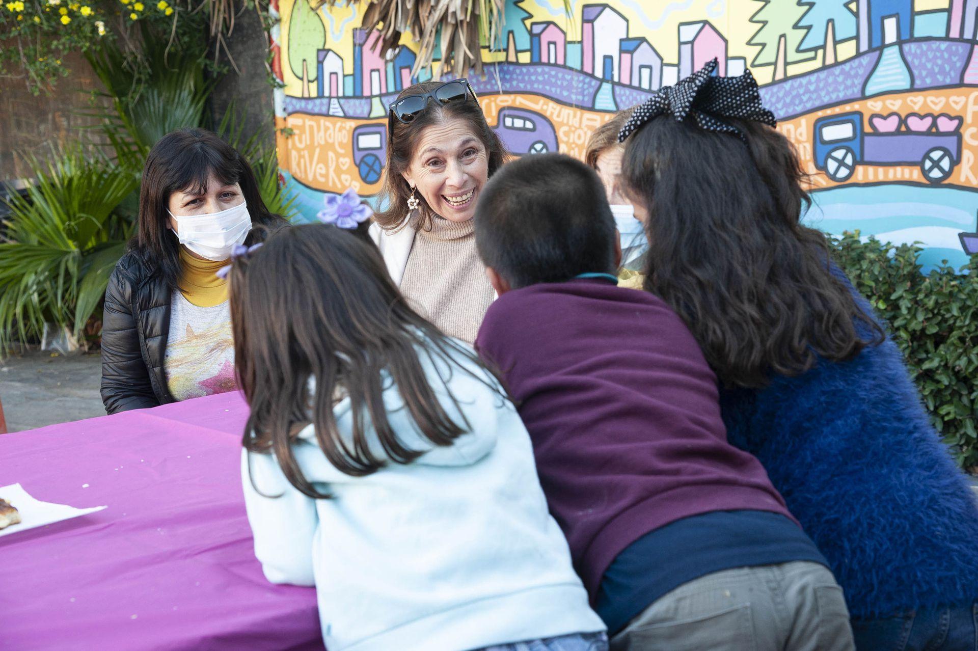 Vicky Acosta (en el centro) responsable del hogar de niños Familias de Esperanza, charla con los tres hermanos que esperan ser adoptados.