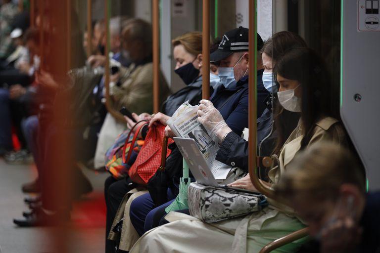 Varias personas vistiendo mascarillas para frenar la propagación del coronavirus viajan en el metro de Moscú, Rusia, el jueves 10 de junio de 2021. (AP Foto/Alexander Zemlianichenko)