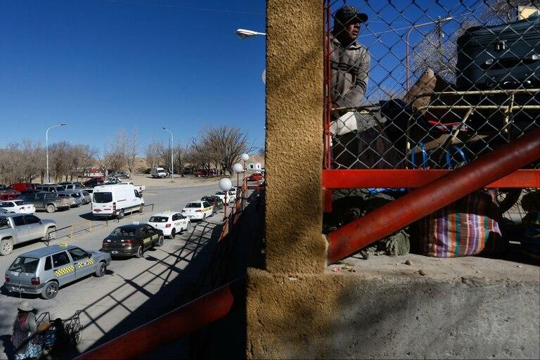 Un hombre arma un bolso mientras taxis esperan pasajeros en el cruce La Quiaca - Villazón